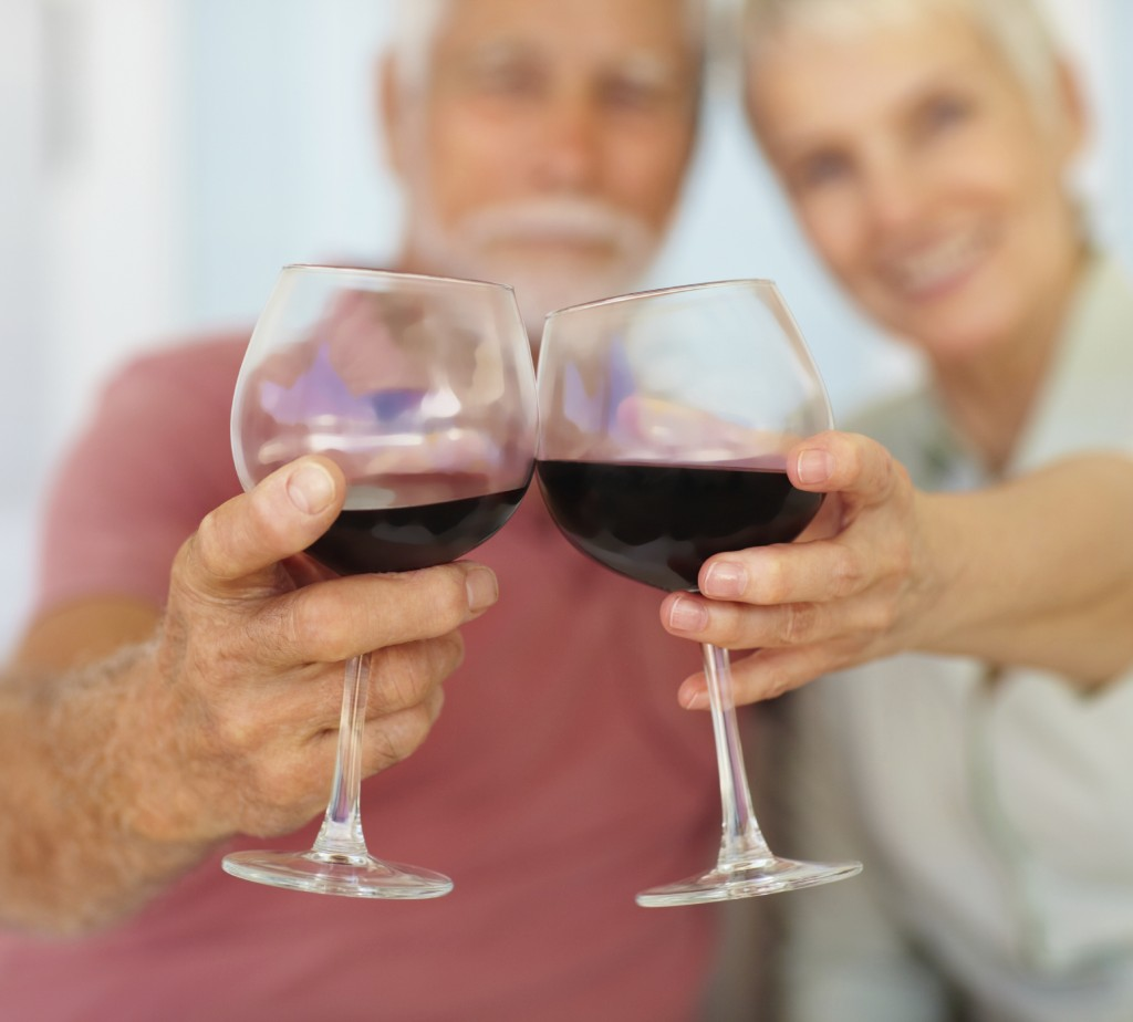 Blur image of an old couple celebrating with a glass of wine
