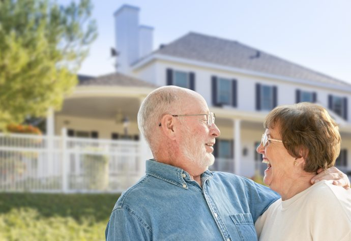 Retired couple smiling in front of family home